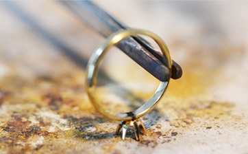 03 指輪のウデと石座をロー付するための準備です。正確な位置へと調整しながら全体のバランスを見る大変繊細な作業になります。