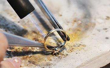 04 ロー付の位置が決まり火を当てながら慎重にウデと石座をロー付していきます。こちらもとても繊細な作業です。